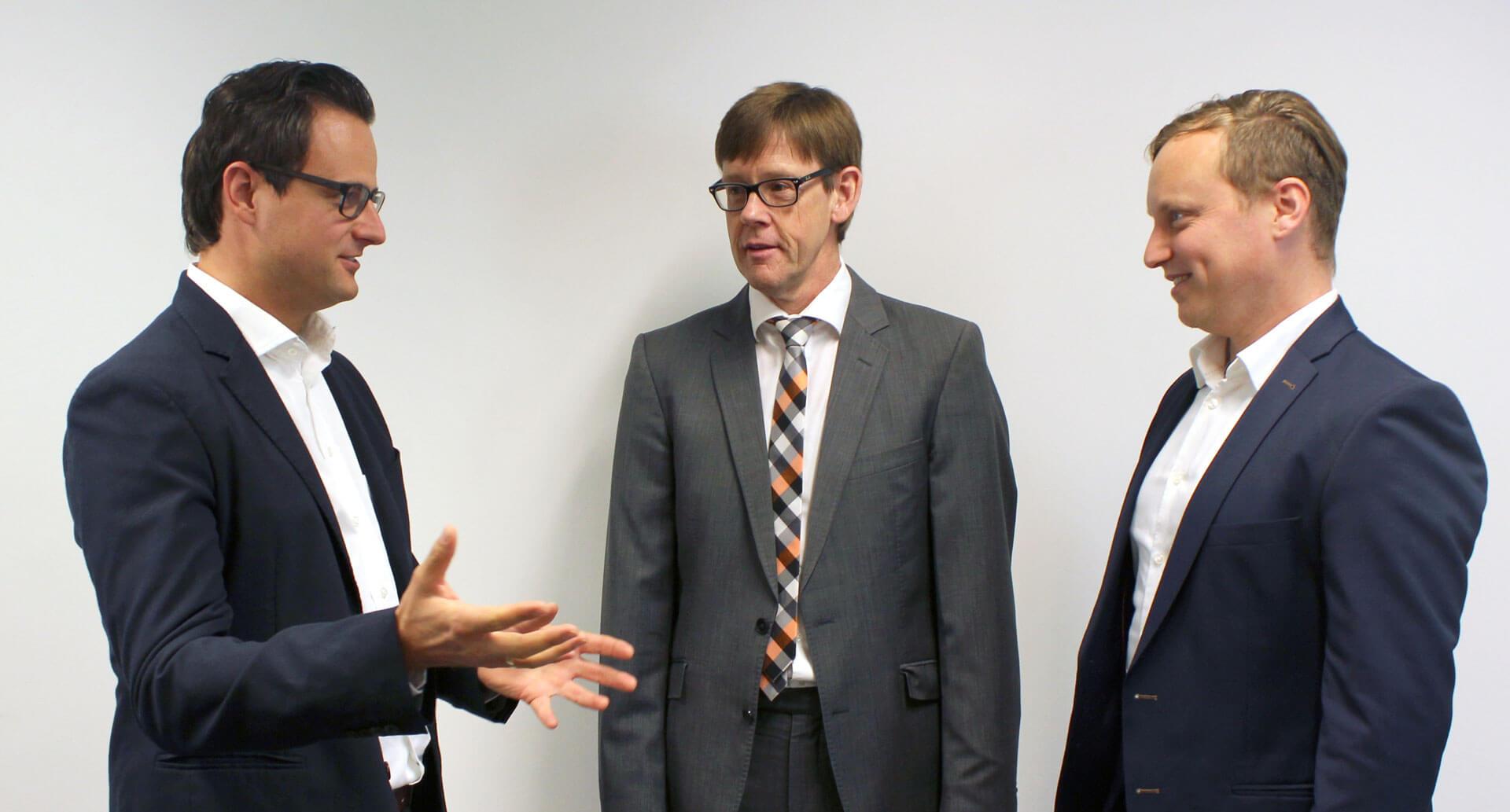 drei Personen führen ein Gespräch